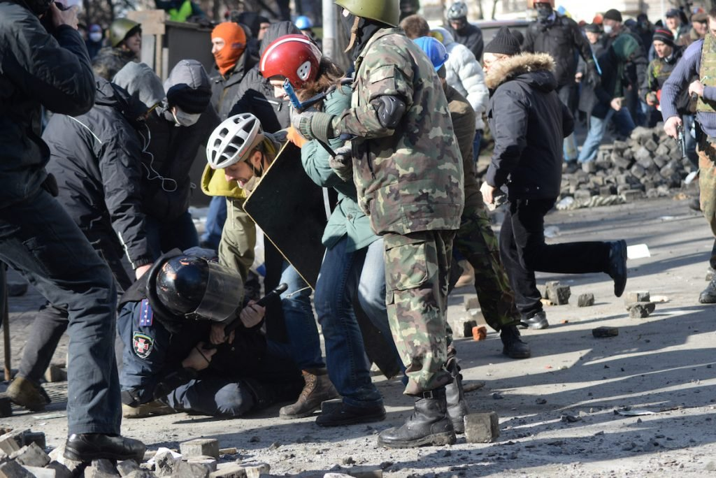 A police officer attacked by protesters during clashes in Ukraine, Kyiv. (Source)