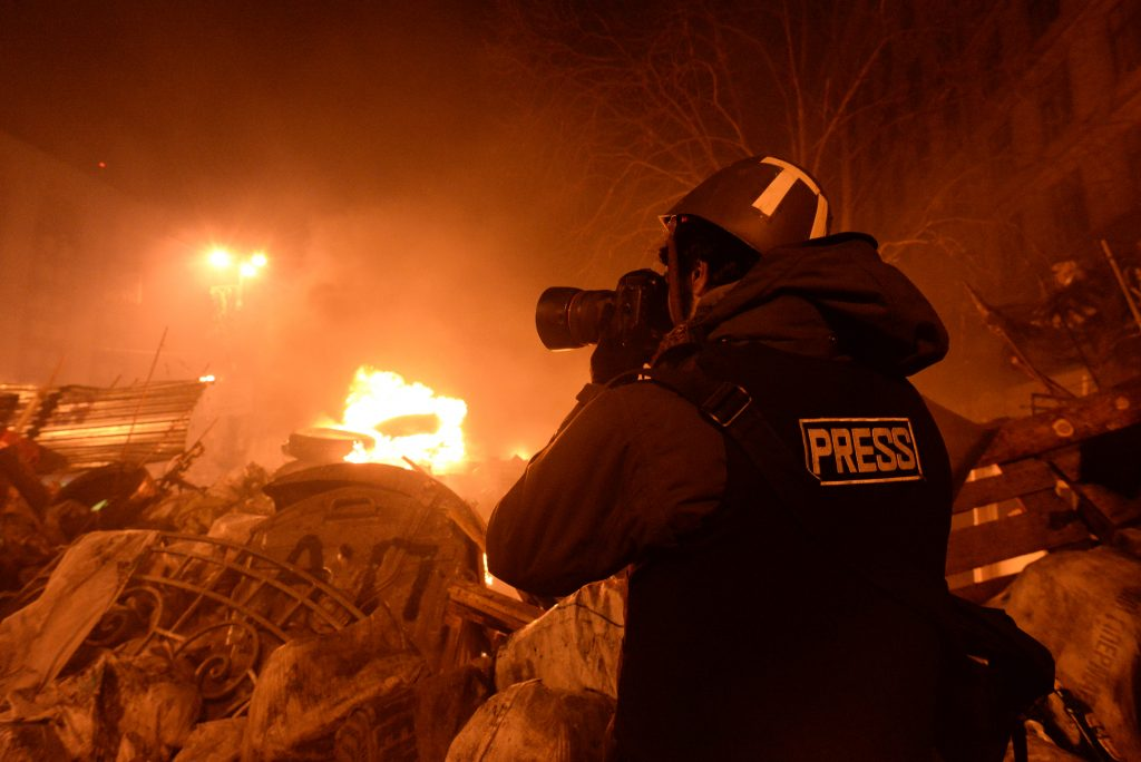 A journalist documenting events at the Independence square in Ukraine. Although newsworthy events like this still get wide coverage by traditional print, TV, and radio, the reach and real-time access provided by emerging new media technologies are slowly