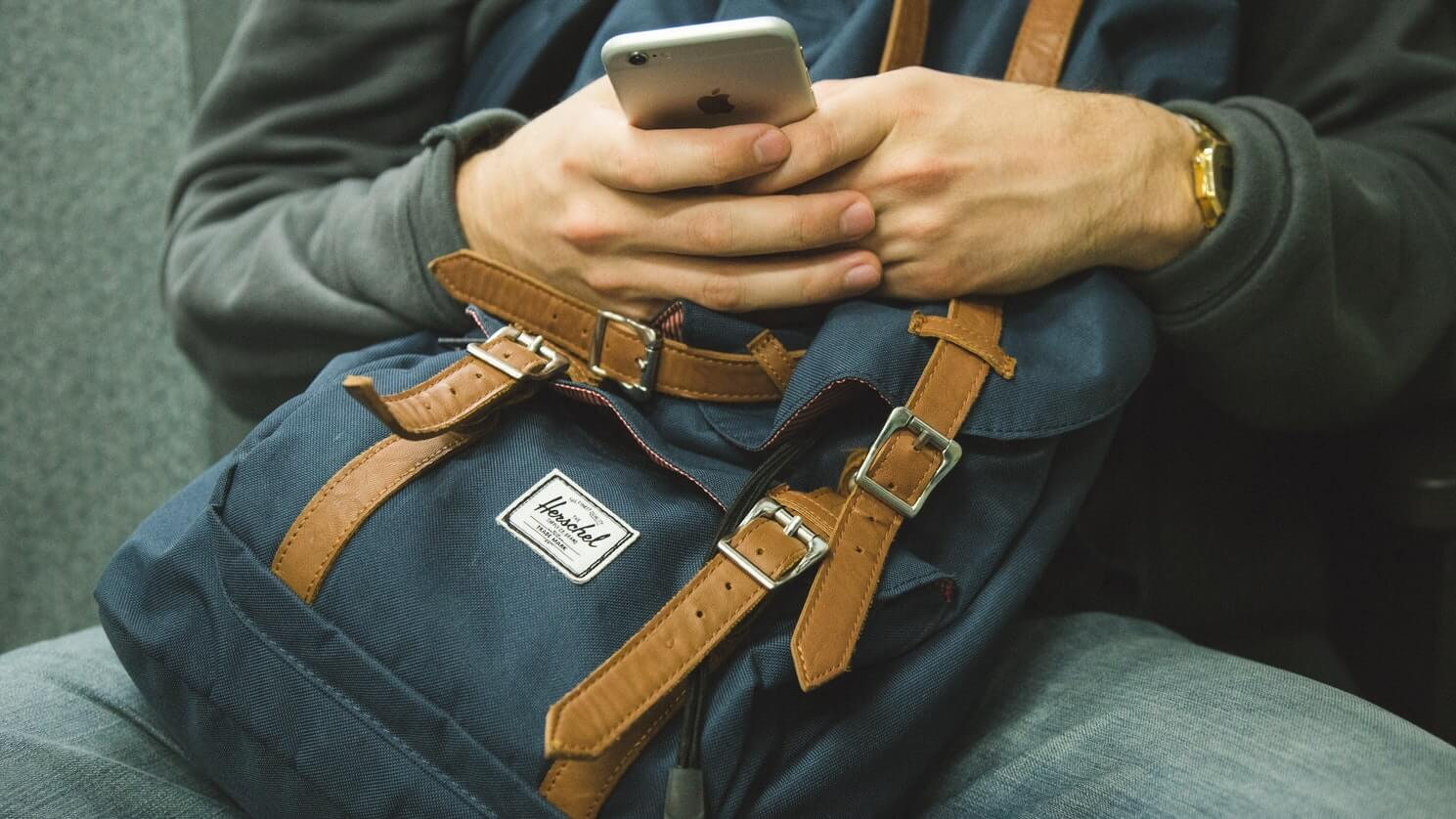 man using phone with backpack