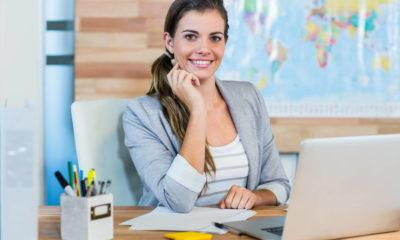 travel agent sitting at her desk with a friendly smile