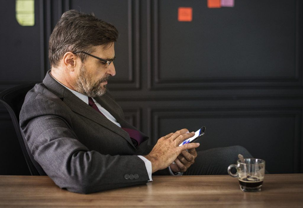 This picture show a man using his smartphone.