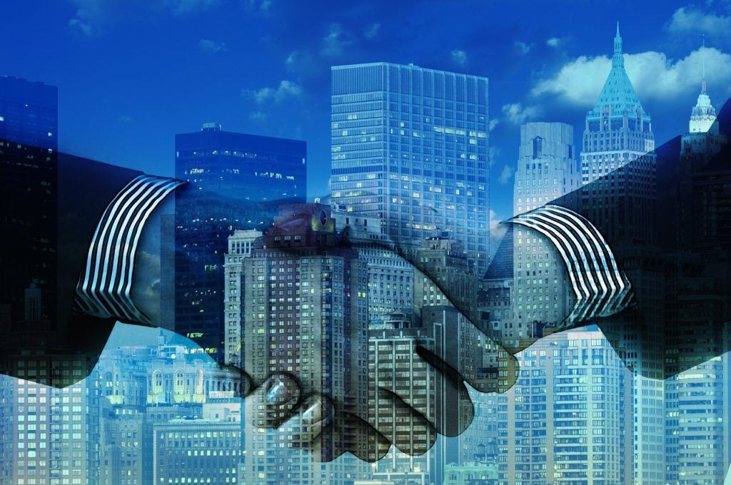 This picture show two people stretching hands, which can be interpreted as the merger of the two companies.