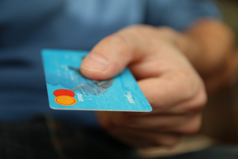 This picture show a man using a credit card.