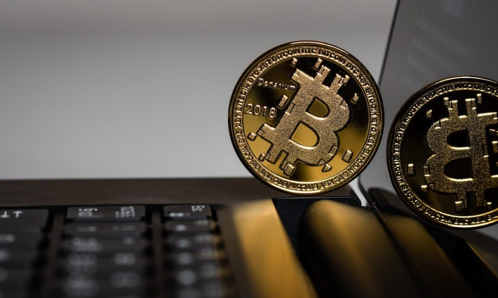 This picture show a bitcoin on top of a laptop.