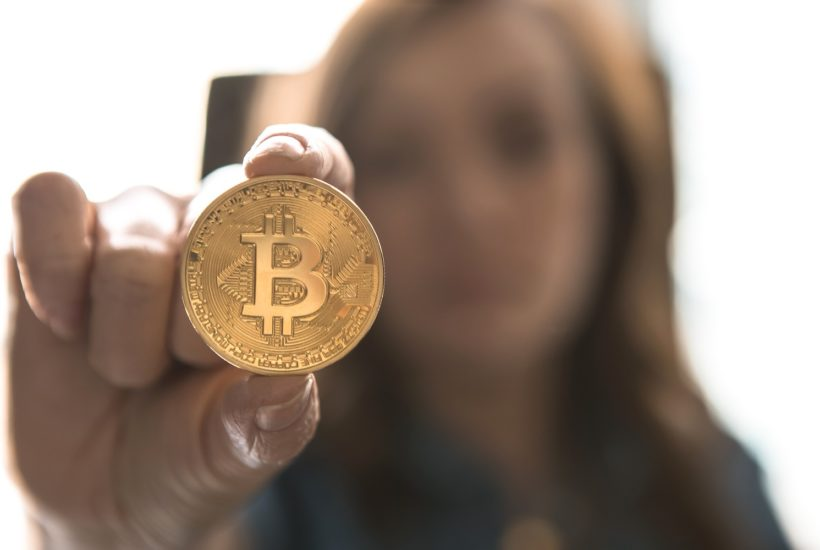 This picture show a woman holding a bitcoin.