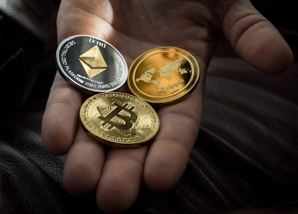 This picture show a hand holding a Bitcoin, Ethereum, and Ripple coin.