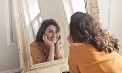 This picture show a woman looking at herself in a mirror.