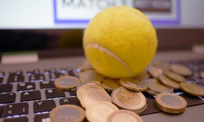 This picture show a tennis balls and some coins on top of a keyboard.