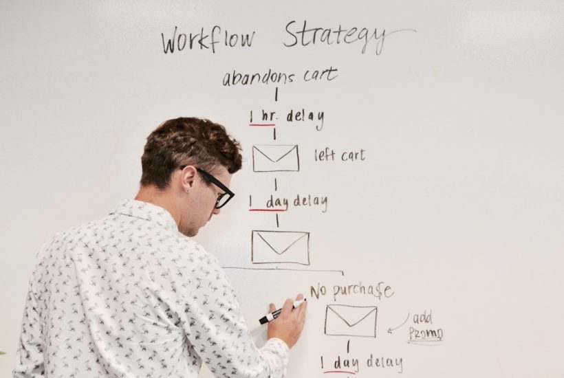 This picture show a man writing on a board.