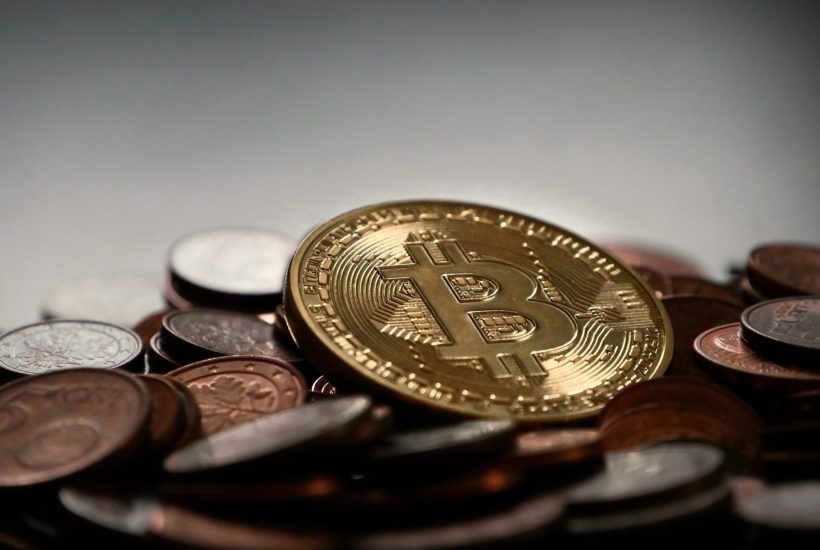 This picture show a bitcoin o top of other coins reflecting the bitcoin's holiday price.