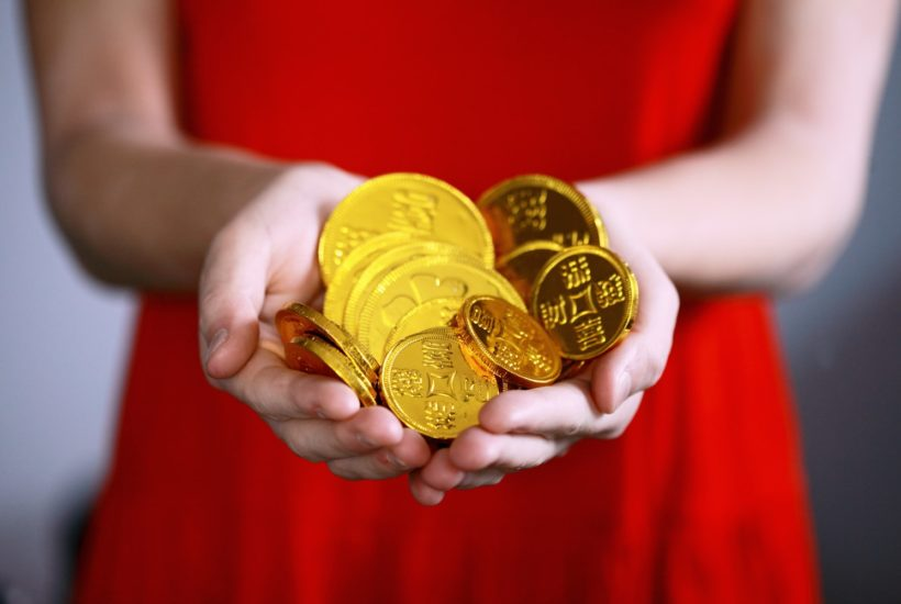 This picture show a woman holding some chinese coins.