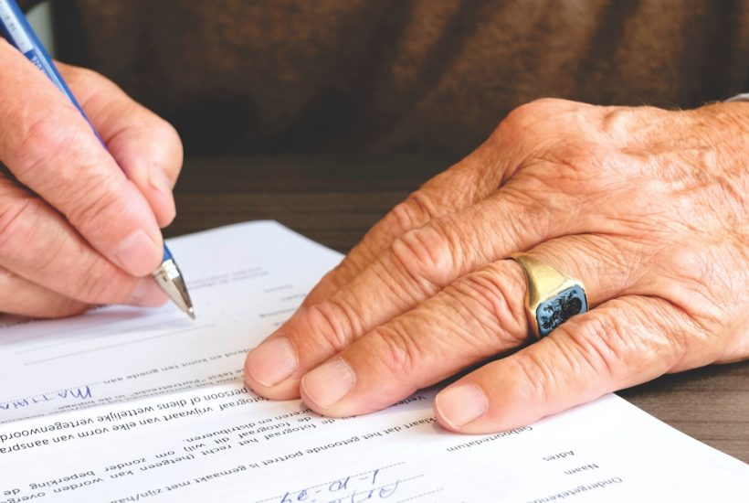 This picture show a man signing some papers.
