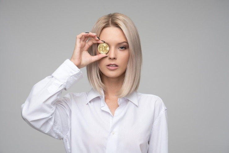 Woman keeping a Bitcoin in her hand