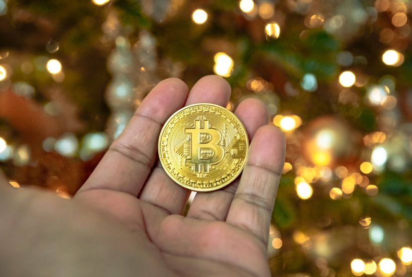 This picture show a man holding a bitcoin and represent the cryptocurrency market.