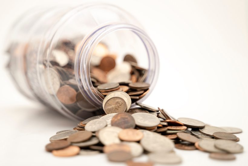This picture show a glass jar full of coins.
