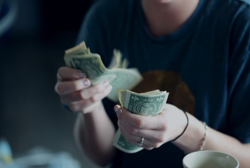 This picture show a person holding some money bills.