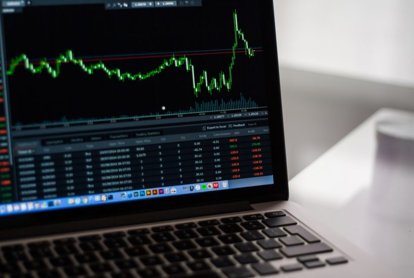 This picture show a laptop with stock market data.