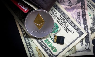 This picture shows a Ethereum coin on top of some dollar bills.