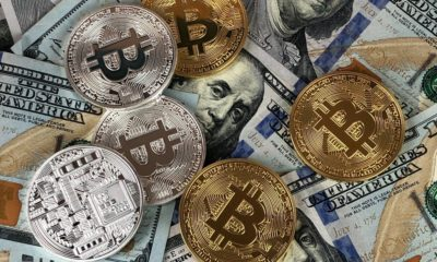 This picture show a couple of bitcoins on top of some dollar bills.
