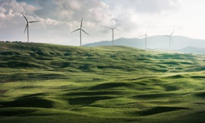 This picture shows a couple of wind turbine on a cliff.