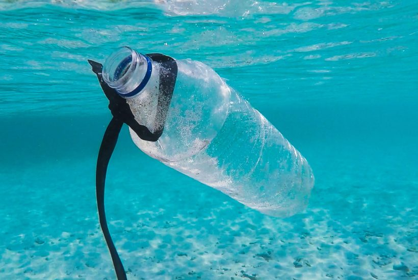 This picture show a plastic bottle in the middle of the ocean.