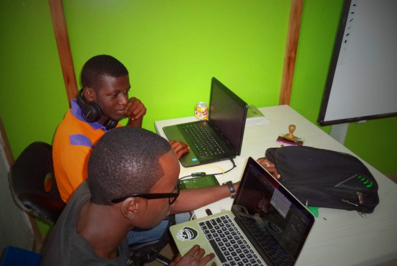 This picture shows two people using a laptop.