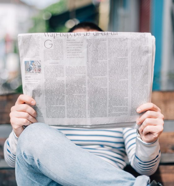 This picture shows a person holding a newspaper.