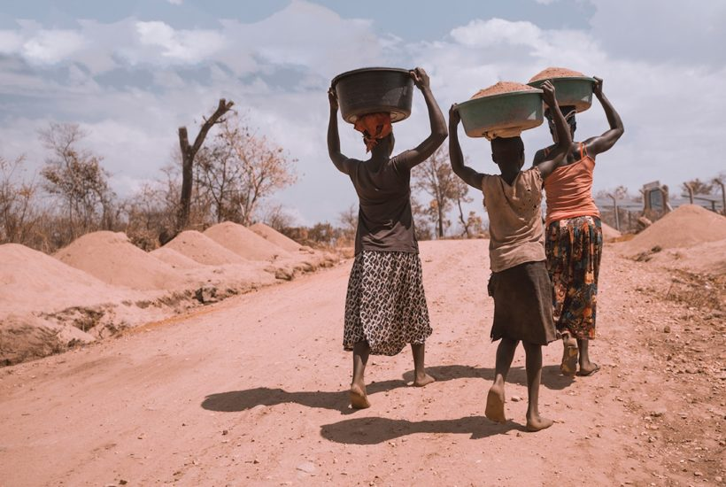 This picture show three African people walking.