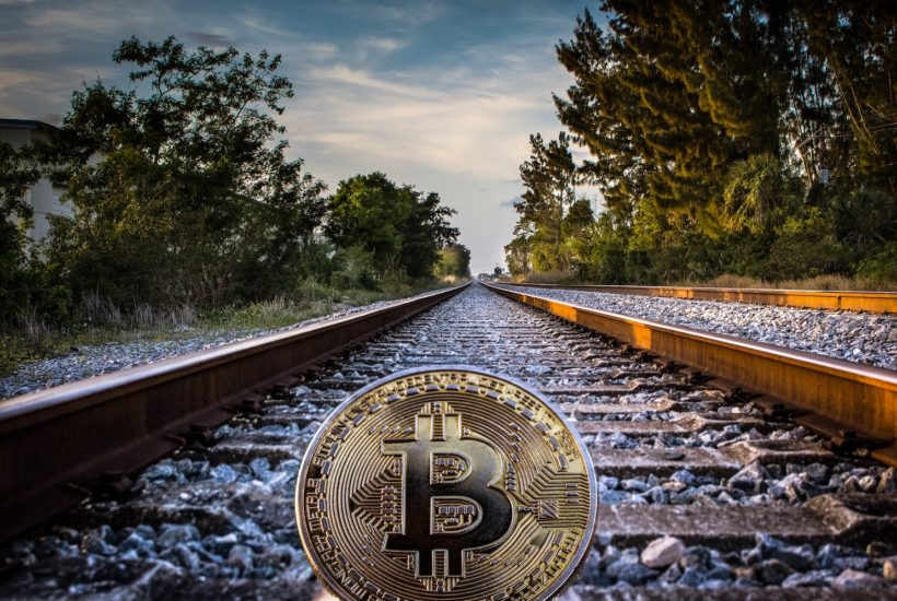 This picture show a bitcoin on a railroad.