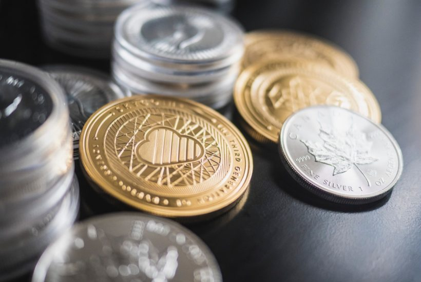 This picture shows a couple of crypto coins on top of a table.