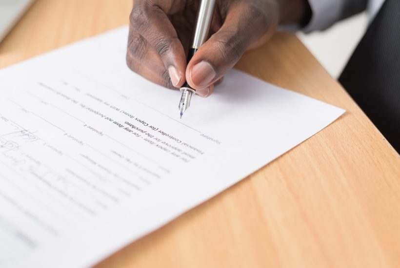 This picture show a person signing a document.