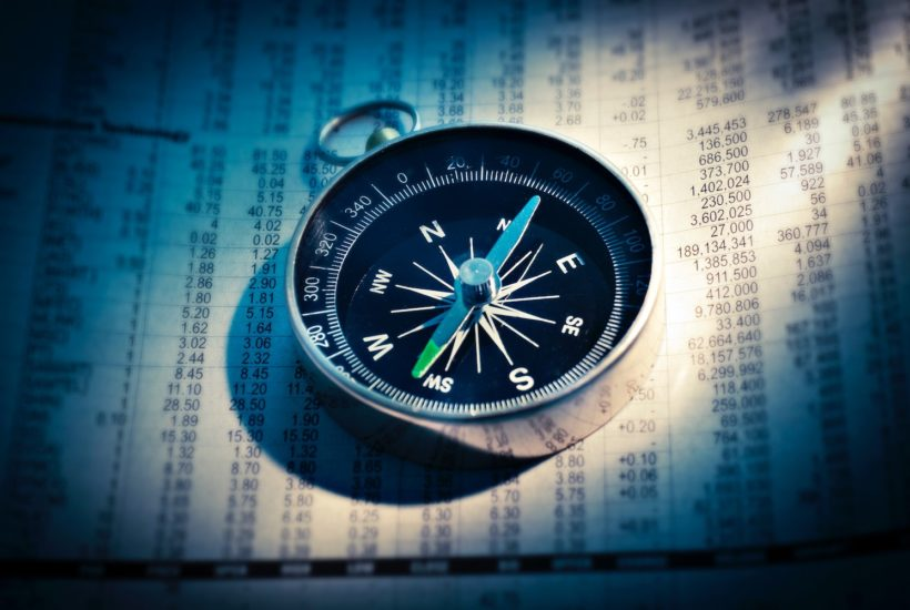 This picture shows a compass on top of some market data.