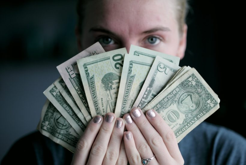 This picture show a person holding some dollars bills.