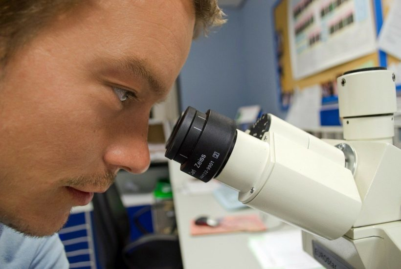 This picture show a person lookin through a microscope.