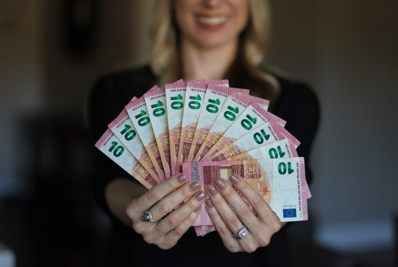 This picture show a woman with a lot of money in her hands.