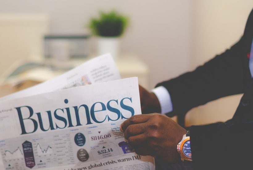 This picture show a person reading a business newspaper.