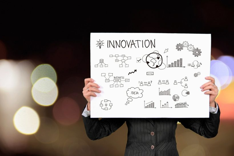 This picture show a person holding an innovation sign.