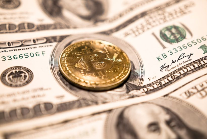This picture show a bitcoin on top of a dollar bill.