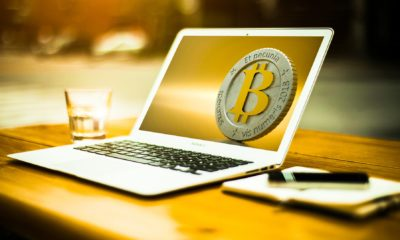 This picture show a laptop with a bitcoin in the screen.