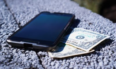 This picture show a smartphone on top of some dollar bills.