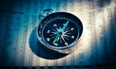 This picture show a compass on top of some market data.