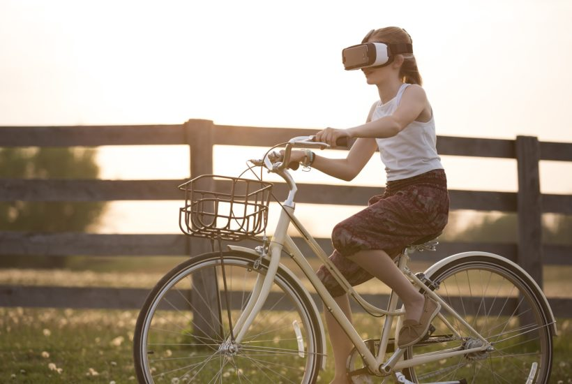 This picture show a woman riding a bike and using a VR set.