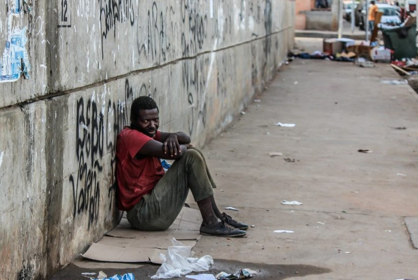 This picture show a person sitting on the street.