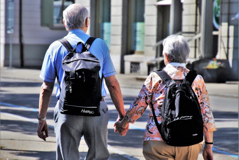 This picture show two eldery people holding hands.