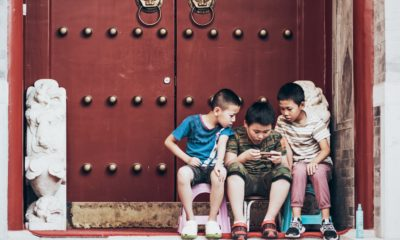This picture show 3 kids playing with their phones.