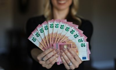 This picture show a woman holding some euro bills.