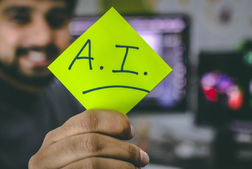 This picture show a persona holding a paper with the AI word written on it.