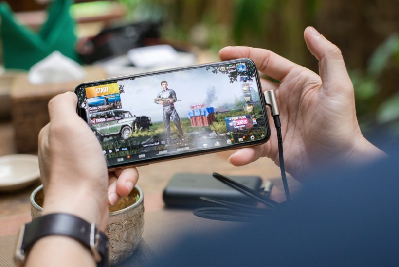 This picture show a persona playing a mobile game.