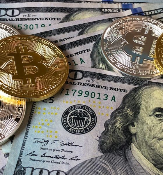 This picture show some bitcoins on top of some dollars.