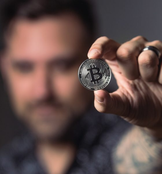 This picture show a person holding a Bitcoin.